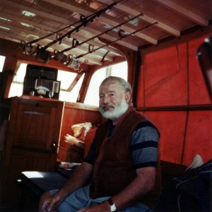 Ernest Hemingway in the cabin of his boat El Pilar. Around his wrist probably an 18c golden, leather band Rolex Oyster from the 1950s
